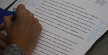 Hand with blue pen giving written feedback on student paper